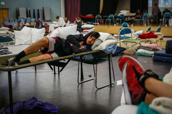 Evacuee Luis Magana, 17, of Santa Rosa, tries to rest on a cot after spending the night at the Petaluma Community Center in Petaluma, Calif., on Tuesday, Oct. 10, 2017. Fires ravaged the area and forced residents to evacuate their homes.