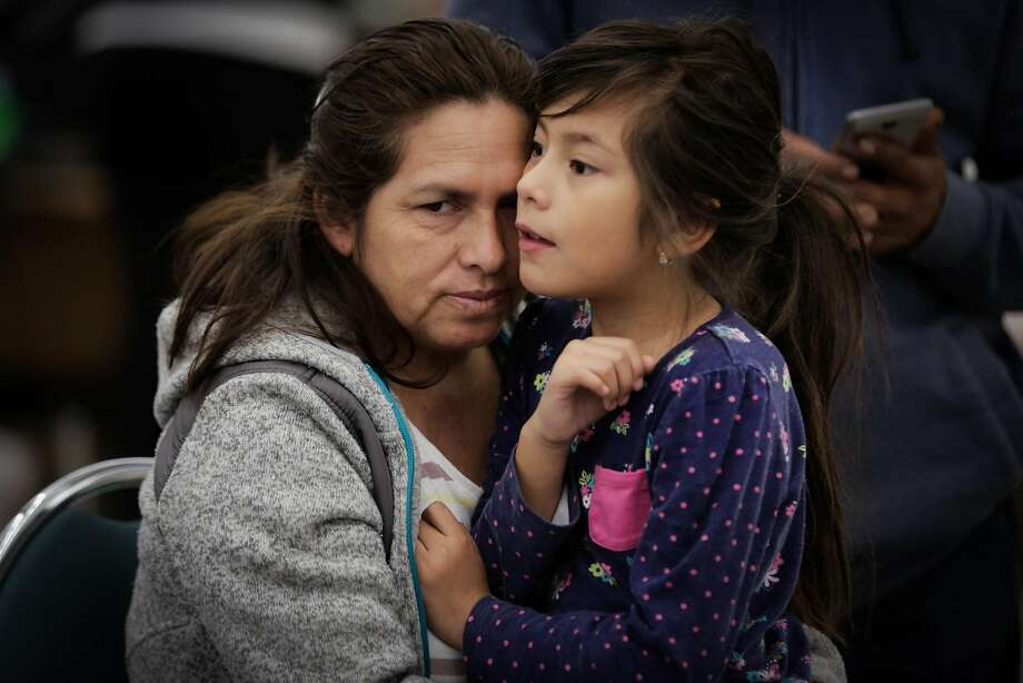 (Left to right) Evacuees Marisela Mata embraces her daughter Marta Mata, 7, at a makeshift evacuation center after fires tore through Santa Rosa and Napa at the Petaluma Community Center in Petaluma, Calif., on Tuesday, Oct. 10, 2017. Photo: Gabrielle Lurie, The Chronicle