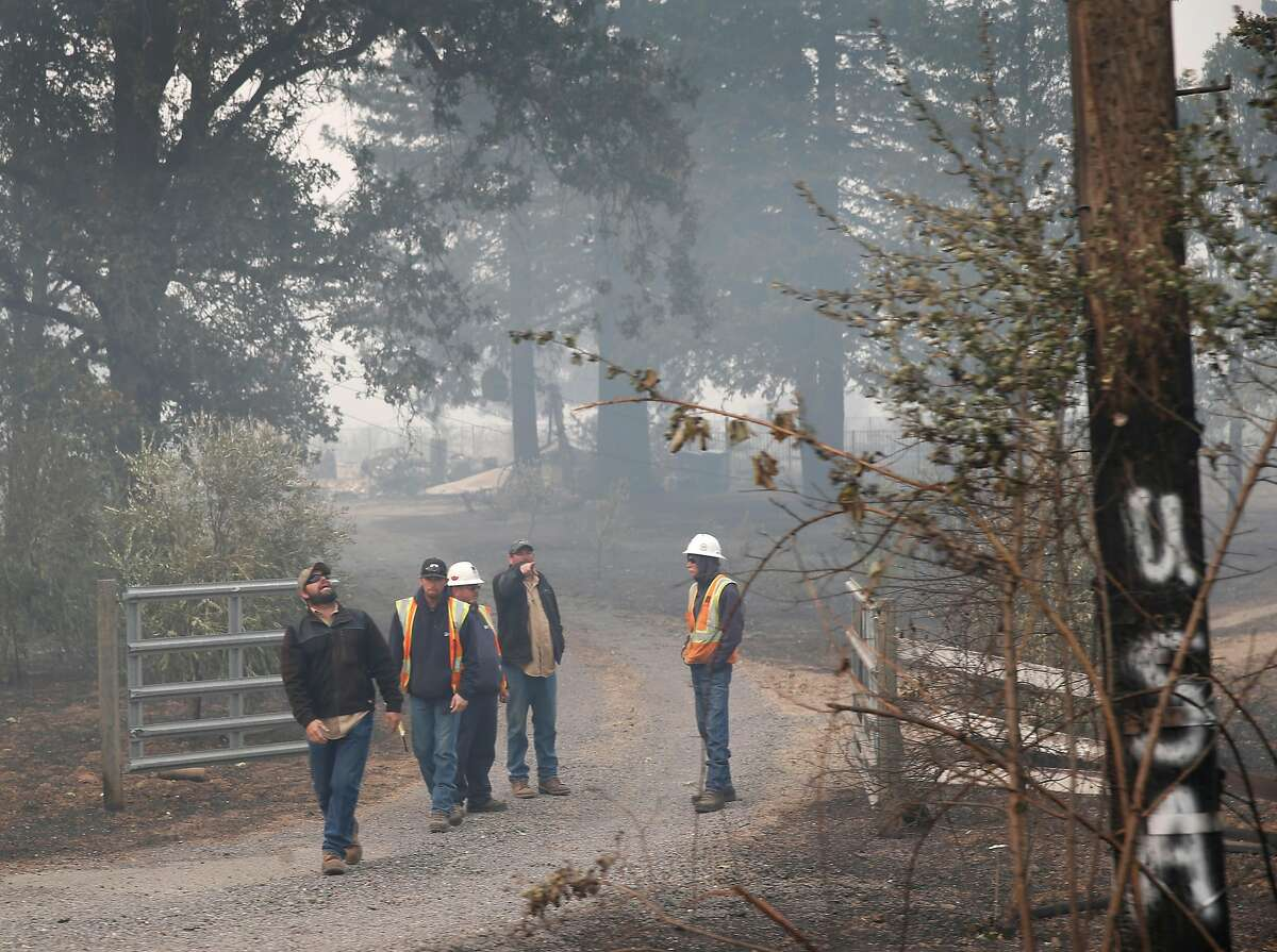 A PG&E crew assesses fire damage to overhead power lines on Tomki Road in Redwood Valley, Calif. on Tuesday Oct. 10, 2017. Authorities have reported at least three people have died and 50 residences have been destroyed by the Redwood Complex Fire.