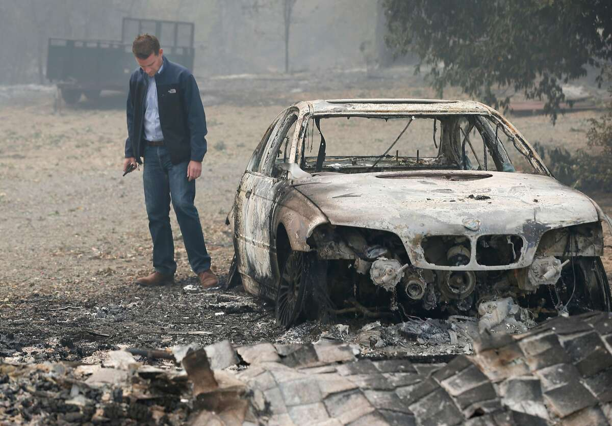 State Sen. Mike McGuire walks past a charred BMW parked off East Road during a tour of the fire zone in Redwood Valley, Calif. on Tuesday Oct. 10, 2017. Authorities have reported at least three people have died and 50 residences have been destroyed by the Redwood Complex Fire.