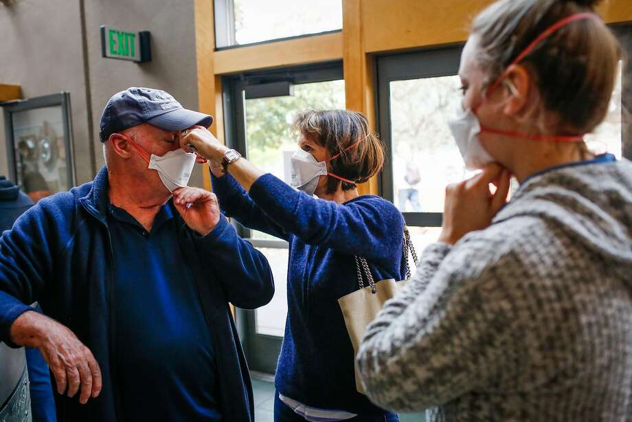 Kathy Devillers (center) helps Gary Michel (left) put on a mask while Kristin Jellison (right) looks on at the Red Cross evacuation center at the Finley Community Center in Santa Rosa, Calif., on Tuesday, Oct. 10, 2017. Fires ravaged the area and forced residents to evacuate their homes. People are wearing masks to protect themselves from thick smoke outside. Photo: Gabrielle Lurie, The Chronicle