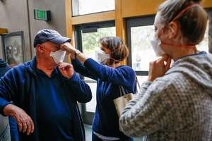 Kathy Devillers (center) helps Gary Michel (left) put on a mask while Kristin Jellison (right) looks on at the Red Cross evacuation center at the Finley Community Center in Santa Rosa, Calif., on Tuesday, Oct. 10, 2017. Fires ravaged the area and forced residents to evacuate their homes. People are wearing masks to protect themselves from thick smoke outside.