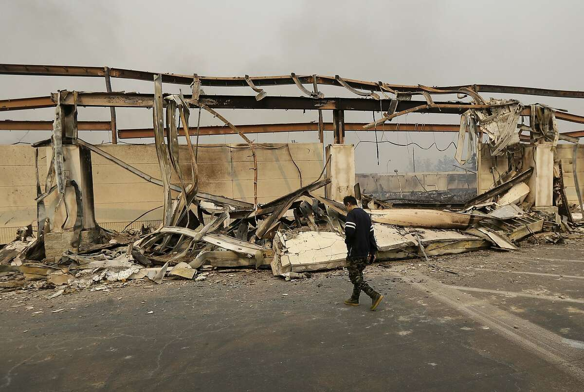A man walks past the front of a Kmart store destroyed by a fire in Santa Rosa, Calif., Monday, Oct. 9, 2017. Wildfires whipped by powerful winds swept through Northern California early Monday, sending residents on a headlong flight to safety through smoke and flames as homes burned. (AP Photo/Jeff Chiu)