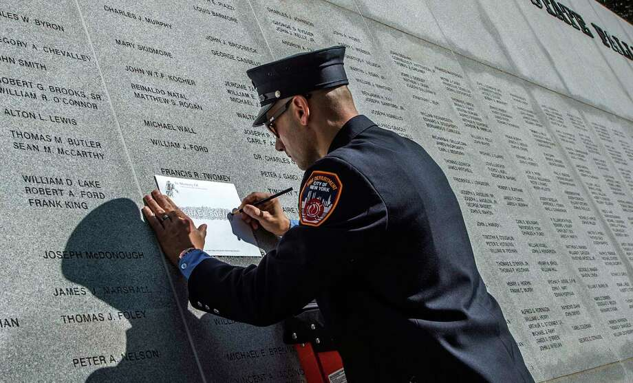 A New York City firefighter makes a rubbing of a name of a loved one on the memorial after the formal proceedings at the 20th Annual New York State Fallen Firefighters Memorial ceremony at the Convention Center at the Empire State Plaza on Tuesday, Oct. 10, 2017, in Albany, N.Y. (Skip Dickstein/Times Union) Photo: SKIP DICKSTEIN, Albany Times Union / 20041795A