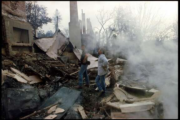 Two men inspect a destroyed house on Alvarado Rd., October 21, 1991, the morning after the Oakland Hills fire tore through the area.