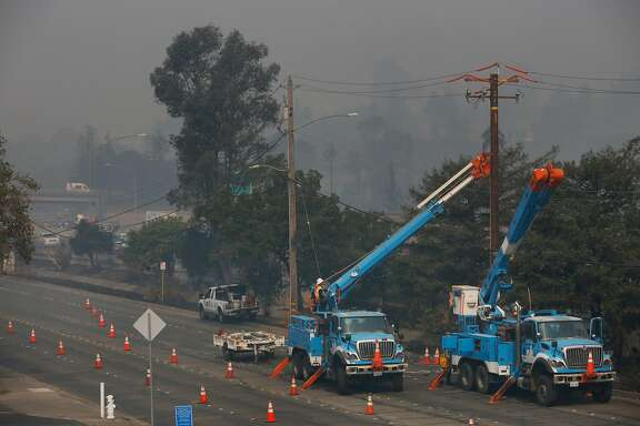 Workers from PG&E work on replacing a downed power line on Cleveland Ave. Oct. 10, 2017 in Santa Rosa, Calif.