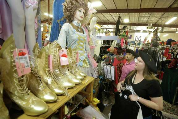 Crystal Martinez and Andy Tran shop for pirate outfits at Frankel's Costume Shop on Tuesday in Houston. This is the last Halloween for the shop.