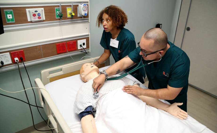 Nurses Carmen Sierra and Jimmy Heredia play the part of nursing students during a simulation at the University of Miami's  simulation in nursing programs. The five-story, 41,000-square-foot, fully equipped facility uniquely designed to replicate the actual flow of activities in real-world hospital, a primary care clinic, and home health settings, and to simulate a fully functioning health care system. (Carline Jean/Sun Sentinel/TNS) Photo: Carline Jean/TNS