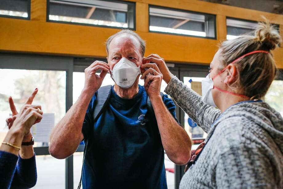 Kristin Jellison (right) helps Mike Jellison secure a mask at the Red Cross evacuation center at the Finley Community Center in Santa Rosa, Calif., on Tuesday, Oct. 10, 2017. Fires ravaged the area and forced residents to evacuate their homes. People are wearing masks to protect themselves from thick smoke outside. Photo: Gabrielle Lurie, The Chronicle