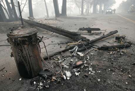 An transformer and utility pole lie in the middle of Tomki Road in Redwood Valley, Calif. on Tuesday Oct. 10, 2017. Authorities have reported at least three people have died and 50 residences have been destroyed by the Redwood Complex Fire.