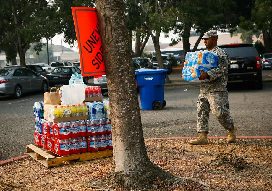 Sgt. Narayan Aman of the 870th Military Police Company carries donated water outside Petaluma Community Center. Photo: Gabrielle Lurie, The Chronicle