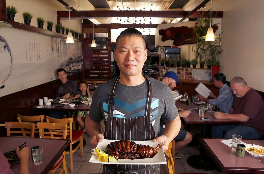 Chef Zhan Shao carries in the showstopper dish, stewed duck in soy sauce, at Jiangnan Cuisine in the Richmond District. Photo: Liz Hafalia, The Chronicle