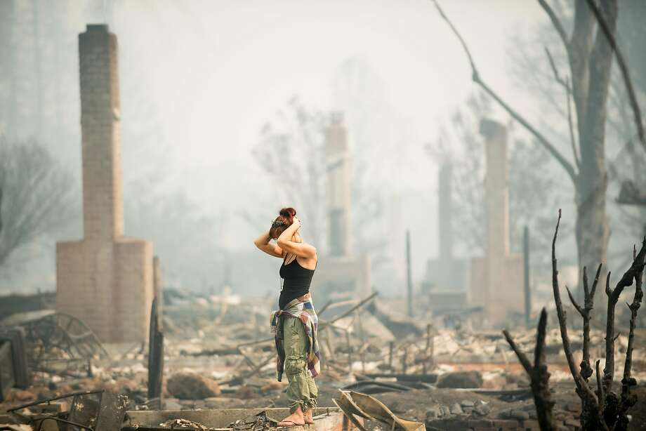 Jeanette Scroggins pauses while searching for signs of her aunt, Karen Aycock, who has been missing since the Tubbs Fire roared through her Coffey Park neighborhood in Santa Rosa, Calif. The following slide shows list the deadliest and most destructive wildfires in California history. Photo: Noah Berger, Special To The Chronicle