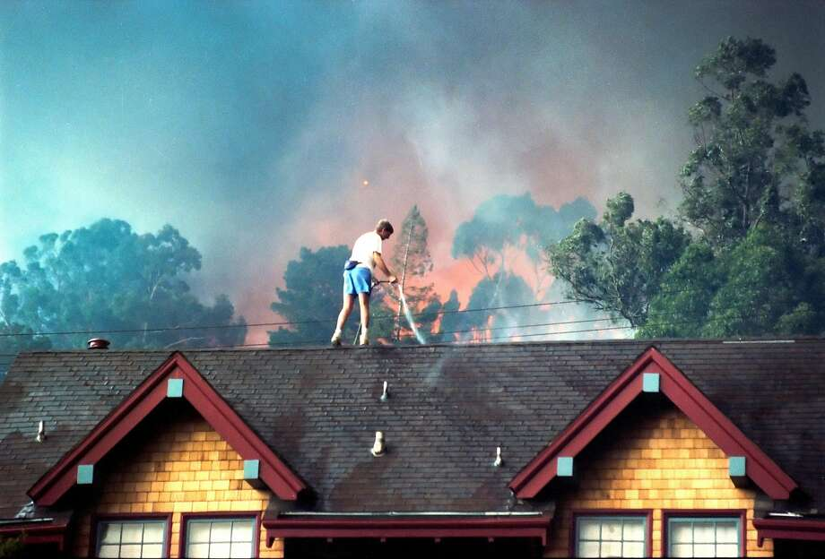 A man uses a garden hose to wet down a roof as the Oakland Hills fire rages in the background on October 20, 1991. Photo: Fred Larson, The Chronicle