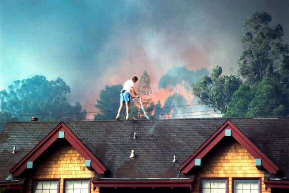 A man uses a garden hose to wet down a roof as the Oakland Hills fire rages in the background on October 20, 1991.