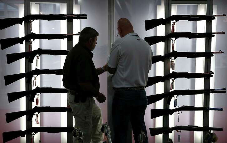 Attendees look at a display of tactical shotguns during the 2013 NRA Annual Meeting and Exhibits at the George R. Brown Convention Center Houston. (Getty Images)