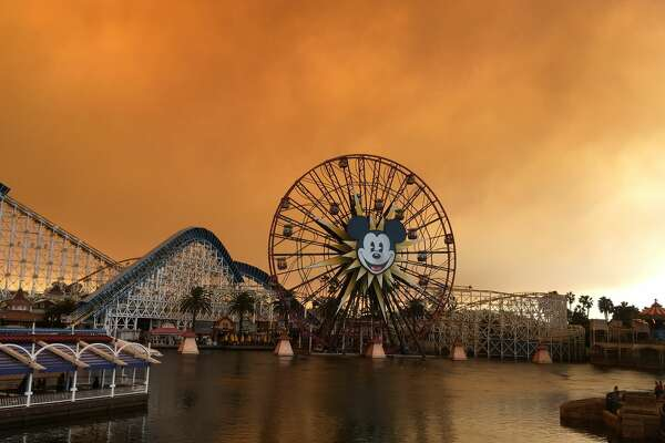 Disneyland in Anaheim, Calif. looked otherworldly Monday, Oct. 9, 2017, as a blanket of smoke hung over the theme park, painting the sky an eerie burnt orange.