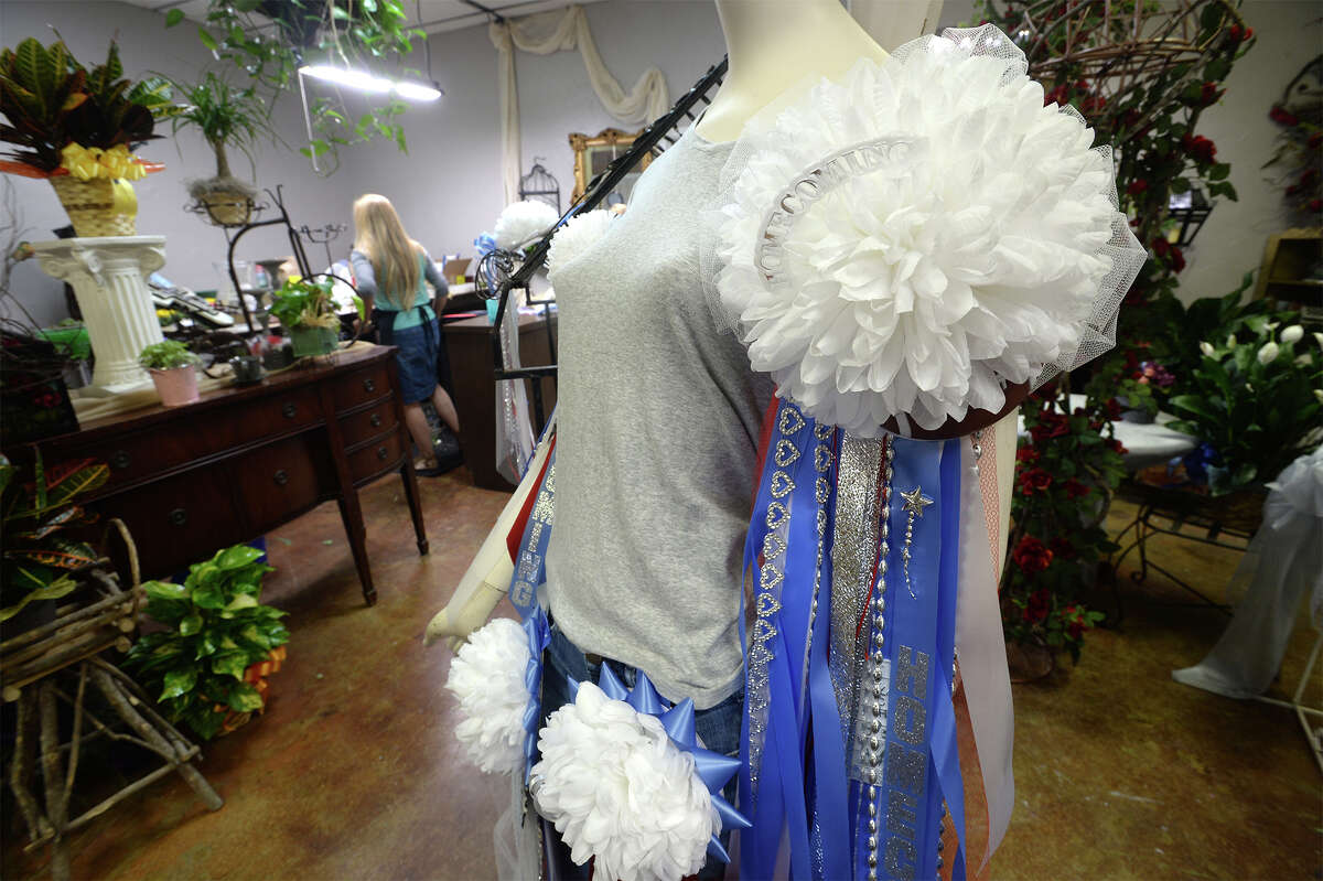 A group of mums hang on a mannequin as Brenda Sims works on flower arrangements at Sherman's Florist on Friday. Photo taken Friday, October 06, 20a7 Guiseppe Barranco/The Enterprise