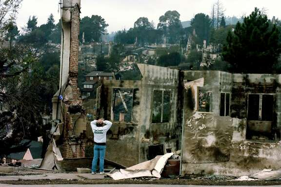A man looks at a destroyed home in Broadway Terrace October 22, 1991, after the Oakland Hills fire tore through the area a few days earlier.