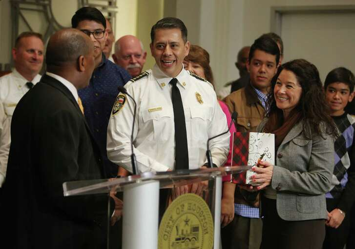 Houston's new fire chief Samuel Pena and his wife, Carolina, hand a Christmas gift of homemade tamales to Mayor Sylvester Turner at the conclusion of Pena's swearing-in ceremony at City Hall, Monday, Dec. 19, 2016, in Houston. ( Mark Mulligan / Houston Chronicle )
