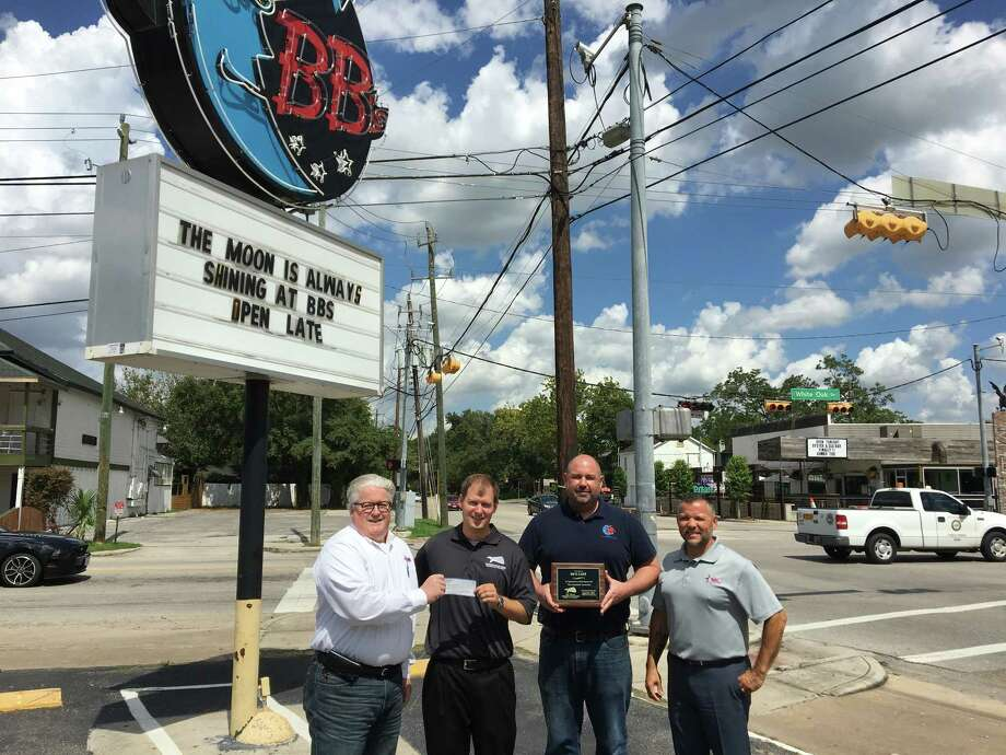 Scott Mitchell, founder of the Kingwood Fallen Heroes,presents a check to James Elmore and Gus Cabaras, of Hope For The Warriors, and a plaque to Ross Vullard, from BB's Café, who donated banquet food for more than 300 participants. Photo: Courtesy