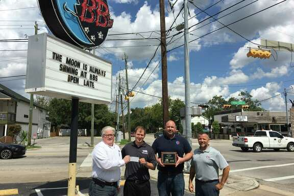 Scott Mitchell, founder of the Kingwood Fallen Heroes,presents a check to James Elmore and Gus Cabaras, of Hope For The Warriors, and a plaque to Ross Vullard, from BB's Café, who donated banquet food for more than 300 participants.