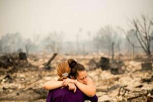 Lori Sarver hugs neighbor Denise Zaleski while searching through the remains of her home in the Coffey Park neighborhood of Santa Rosa, Calif., on Tuesday, Oct. 10, 2017. Both lost their homes as the Tubbs fire roared though the area early Monday morning.