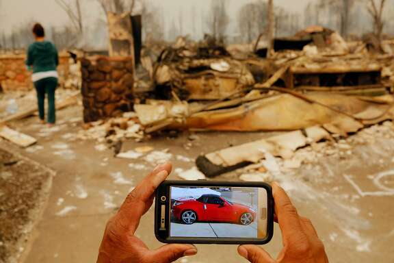 Keith Norris shows what his car destroyed in the fire looked like before the fire, in Santa Rosa, Ca., on Monday October 9, 2017. Massive wildfires ripped through Napa and Sonoma counties early Monday, destroying hundreds of homes and businesses on Monday October 9, 2017