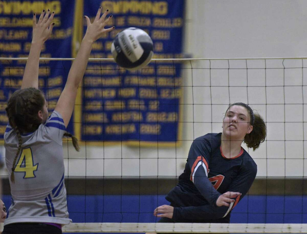 Danbury's Catrina Sullivan (24) pikes the ball past Brookfield's Holly Fleming (4) in the girls volleyball match between Danbury and Brookfield high schools, Tuesday afternoon, October 10, 2017, at Brookfield High School, in Brookfield, Conn.