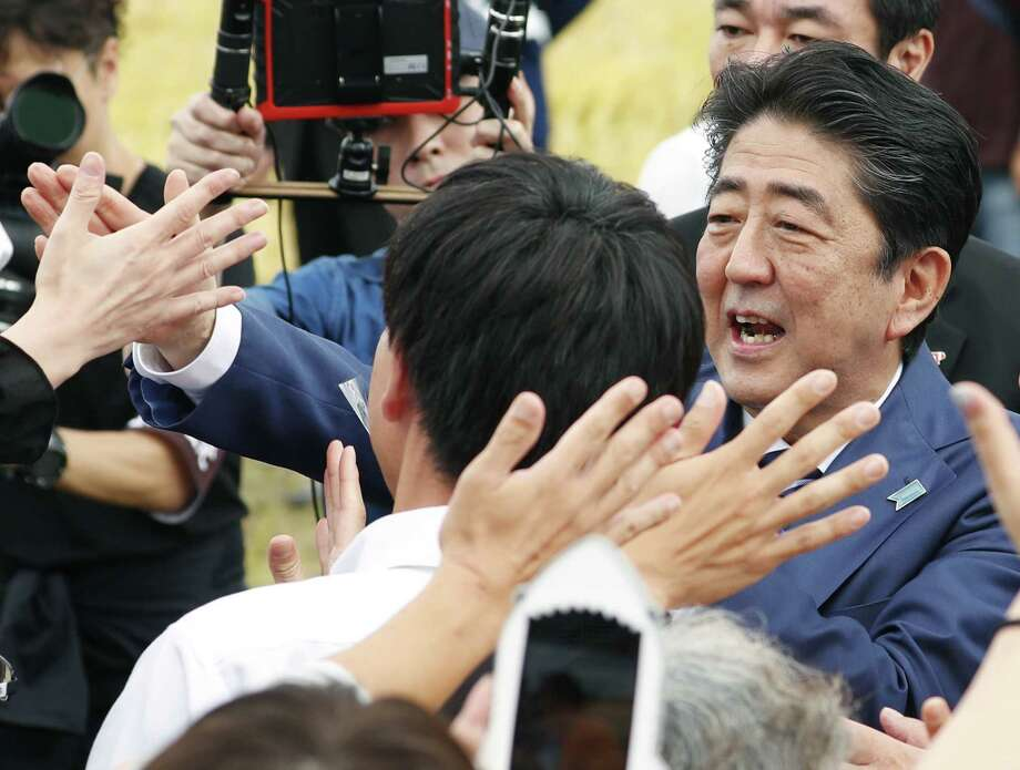 Japanese Prime Minister and leader of ruling Liberal Democratic Party Shinzo Abe, right,  greets the crowd, during his party's election campaign in Fukushima, eastern Japan, Tuesday, Oct. 10, 2017. Hundreds of candidates have taken to the streets as a 12-day official campaigning for Japan's Oct. 22 lower house election kicked off, with Prime Minister Abe's ruling party facing challenges from regrouped opposition forces. (Hironori Asakawa/Kyodo News via AP) Photo: Hironori Asakawa, SUB / Kyodo News