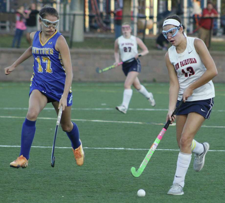 New Fairfield's Sydney Collentine, right, looks for an open teammate as Newtown's Katherine Dirga moves in to defend during the field hockey game at New Fairfield High School Oct. 10, 2017. Photo: Richard Gregory / Richard Gregory