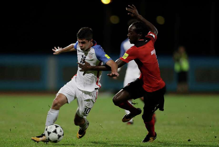 United States' Christian Pulisic, left, fight for the ball with Trinidad and Tobago's Nathan Lewis during a 2018 World Cup qualifyingsoccermatch in Couva, Trinidad, Tuesday, Oct. 10, 2017. Photo: Rebecca Blackwell, AP / Copyright 2017 The Associated Press. All rights reserved.