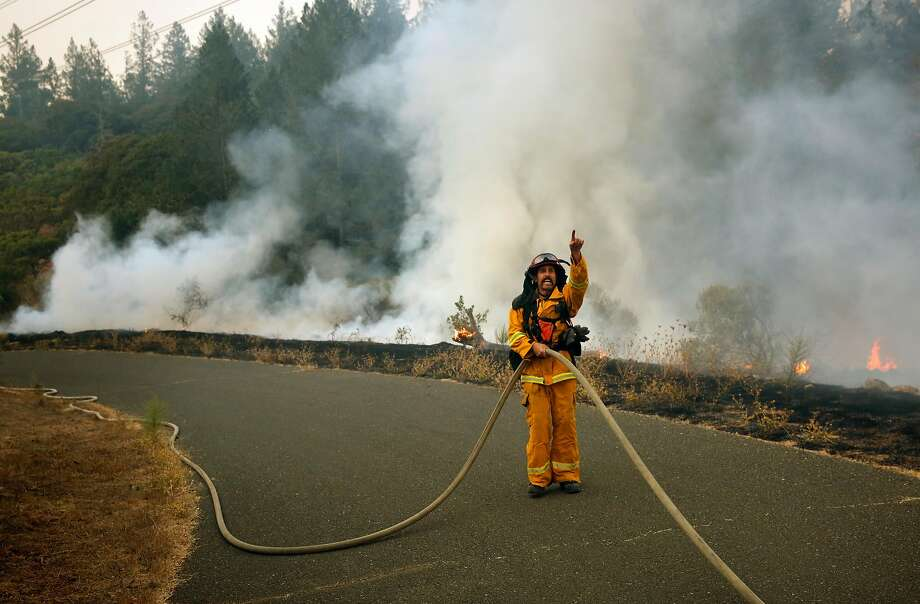 Captain Mike Harrison of Santa rosa fire directs his team of firefighters in containing a small roadside fire in the Oakmont neighborhood of Santa Rosa, Calif. on Tuesday October 10, 2017. Massive wildfires ripped through Napa and Sonoma counties, destroying hundreds of homes and businesses on Monday morning. Photo: Michael Macor, The Chronicle