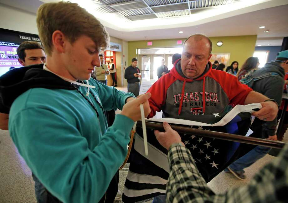 Phillip Maresh, from Pearland, and Rob Farrer, from Lubbock, hang up a thin blue line flag to honor Floyd East Jr., the Texas Tech University police officer shot and killed on Monday. Hollis Daniels, a student at the school, has been arrested. Photo: Brad Tollefson, MBI / Lubbock Avalanche-Journal