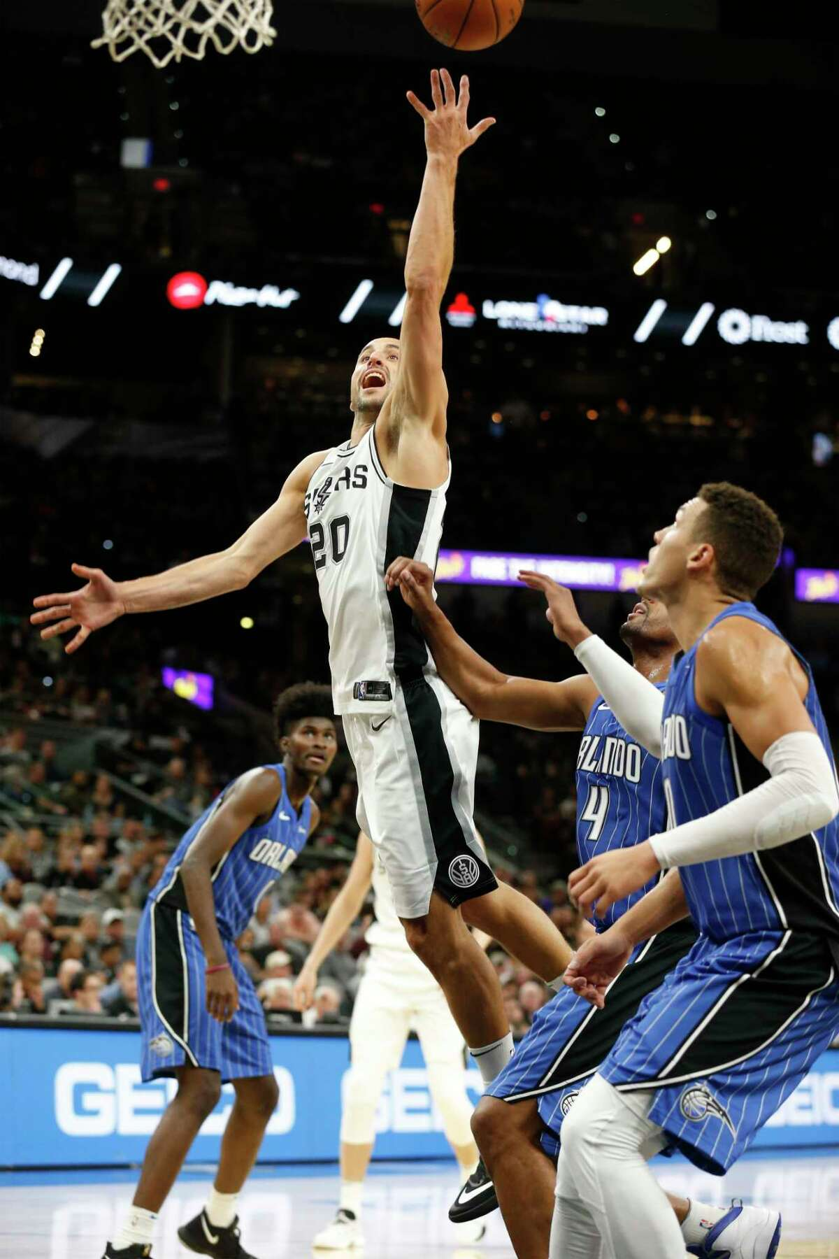 Spurs' Manu Ginobili (20) lays up a shot against Orlando Magic's Arron Afflalo (04) and Aaron Gordon (00) during their pre-season game at the AT&T Center on Tuesday, Oct. 10, 2017.