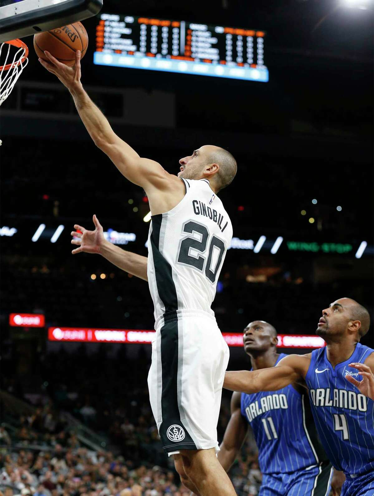 Spurs' Manu Ginobili (20) slips past for a score against Orlando Magic's Arron Afflalo (04) and Bismack Biyombo (11) during their pre-season game at the AT&T Center on Tuesday, Oct. 10, 2017.