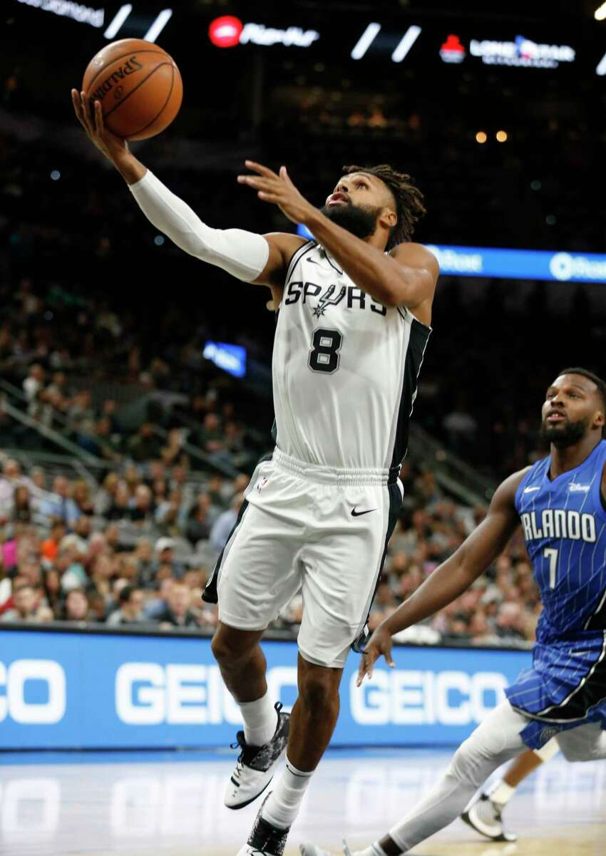 Spurs' Patty Mills (08) lays up a shot against Orlando Magic's Shelvin Mack (07) during their pre-season game at the AT&T Center on Tuesday, Oct. 10, 2017.