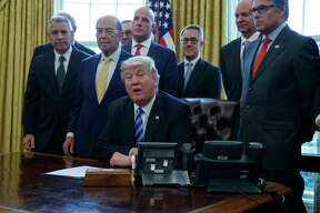 FILE - In this March 24, 2017 file photo, President Donald Trump announces the approval of a permit to build the Keystone XL pipeline, clearing the way for the $8 billion project, in the Oval Office of the White House in Washington. From left are TransCanada CEO Russell K. Girling, Commerce Secretary Wilbur Ross and Energy Secretary Rick Perry. Justice Department attorneys are due to appear in federal court in Montana on Wednesday, Oct. 11, 2017 to argue for the dismissal of two lawsuits that challenged the permit for the 1,179-mile pipeline.  (AP Photo/Evan Vucci, File)