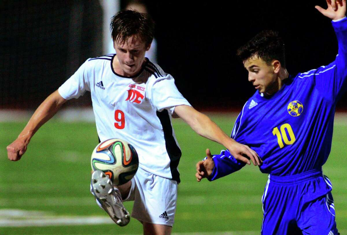 Masuk's Kyle Konkol, left, intercepts the ball during boys soccer action in Monroe, Conn., on Tuesday Oct. 10, 2017. At right is Newtown's Owen Baillargeon.
