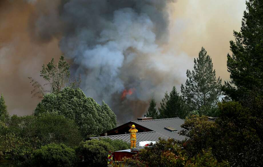 A house in the Oakmont neighborhood is endangered by nearby flames. While a single wildfire can't cause insurance rates to spike, multiple disasters over the course of years could cause insurers to raise rates or leave markets. Photo: Michael Macor, The Chronicle