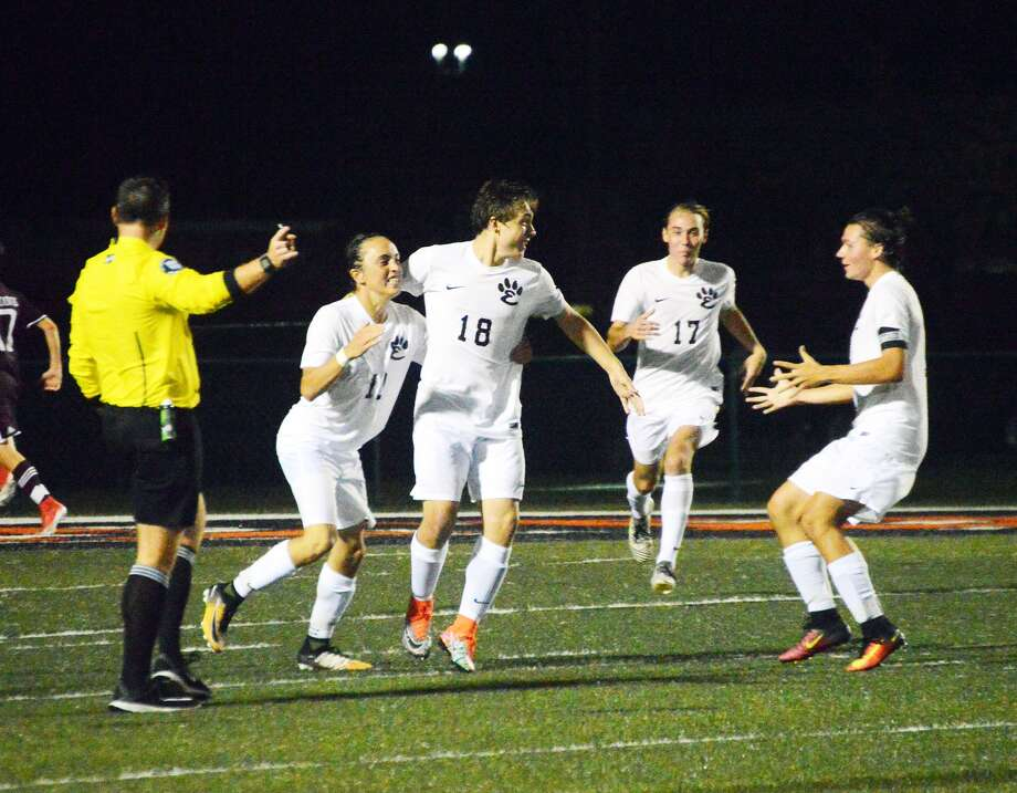 Edwardsville's Ethan Miracle, left, and Kyle Wright, right, celebrate after Cooper Nolan, center, scores to put the Tigers ahead 2-1 against Belleville West. Bayne Noll (No. 17) is in the background.