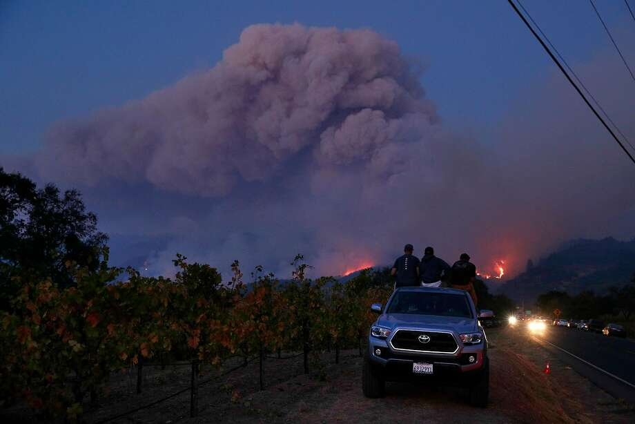 L-R, Joe Lee, Nick Woodle, and Jordan Winslow watch as a fire grows along the ridge neaer Highway 12 outside Eldridge, Calif., on Tuesday, October 10, 2017. The Napa and Sonoma valleys continue to be under threat from several fires as some communities begin  to assess the impact of the fires. Photo: Carlos Avila Gonzalez, The Chronicle