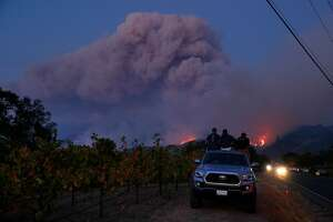 L-R, Joe Lee, Nick Woodle, and Jordan Winslow watch as a fire grows along the ridge neaer Highway 12 outside Eldridge, Calif., on Tuesday, October 10, 2017. The Napa and Sonoma valleys continue to be under threat from several fires as some communities begin  to assess the impact of the fires.
