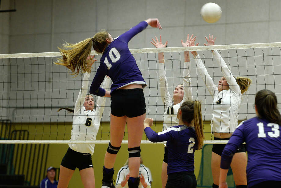 Port Neches-Groves' Elizabeth Bolyard hits the ball against Nederland defenders Karley McGill, Mackenzie MacFarlane and Meg Sheppard in a volleyball game on Tuesday evening.  Photo taken Tuesday 10/10/17 Ryan Pelham/The Enterprise Photo: Ryan Pelham / ©2017 The Beaumont Enterprise/Ryan Pelham