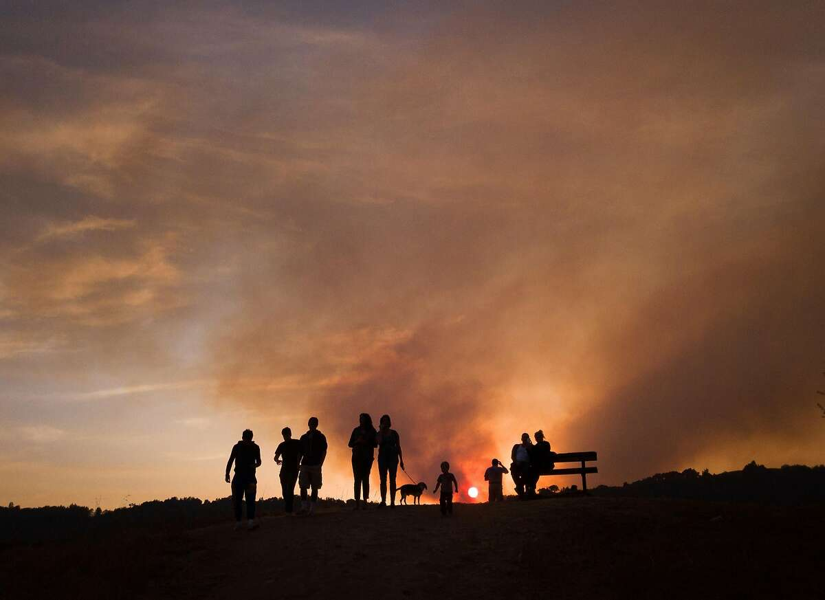 People watch the sunset through smoke in the air from a fire on Mount Veeter in Napa, Calif. on Tuesday, October 10, 2017.