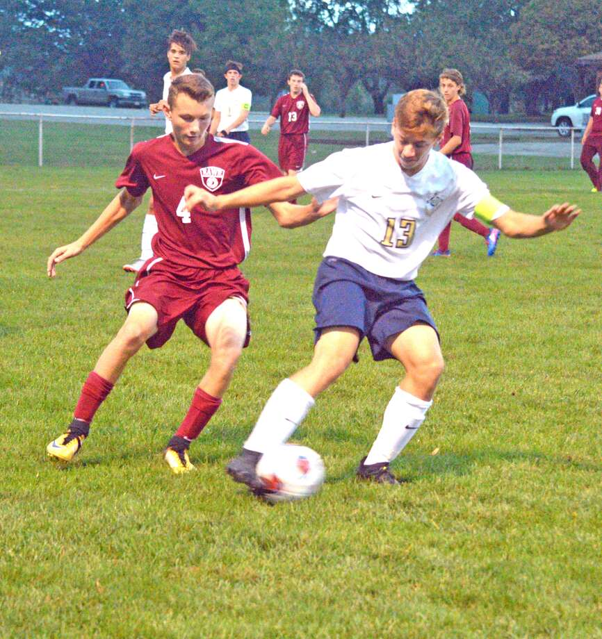Father McGivney senior Dan Jones, right, tries to work his way past an East Alton-Wood River defender during the first half of Tuesday's Class 1A regional semifinal at Gordon Moore Park.