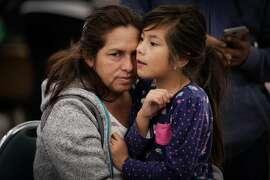 (l-r) Evacuees Marisela Mata embraces her daughter Marta Mata, 7, at a makeshift evacuation center after fires tore through Santa Rosa and Napa at the Petaluma Community Center in Petaluma, Calif., on Tuesday, Oct. 10, 2017.