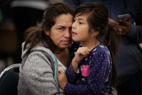 (l-r) Evacuees Marisela Mata embraces her daughter Marta Mata, 7, at a makeshift evacuation center after fires tore through Santa Rosa and Napa at the Petaluma Community Center in Petaluma, Calif., on Tuesday, Oct. 10, 2017.