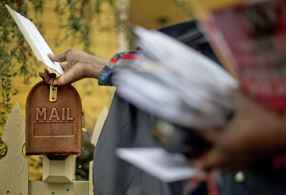 A U.S. Postal Service letter carrier delivers mail in Atlanta. Photo: David Goldman / Associated Press / AP