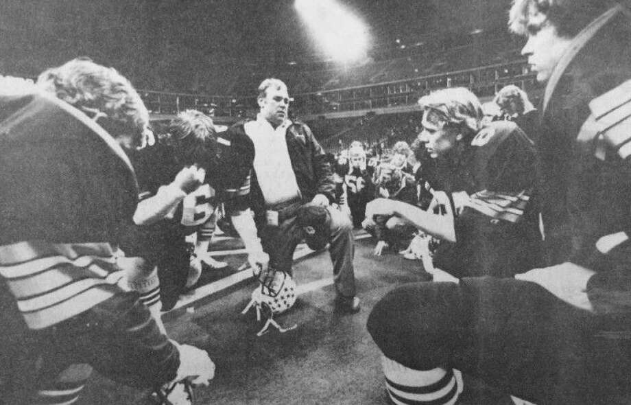Coach Buddy Moorhead consoles his Conroe Tigers with prayer after a last-second 15-11 loss to Dallas Carter in a regional playoff game at Texas Stadium in Irving in the early 1980s. Moorhead, a 1957 Conroe High graduate, was head coach at Conroe High from 1980 until his death in June 1983.